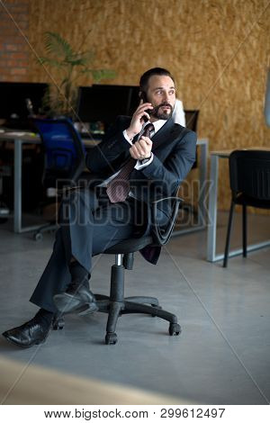 Handsome Young Smiling Businessman Working In Office. Siotting On Chair And Talking Over Phone.