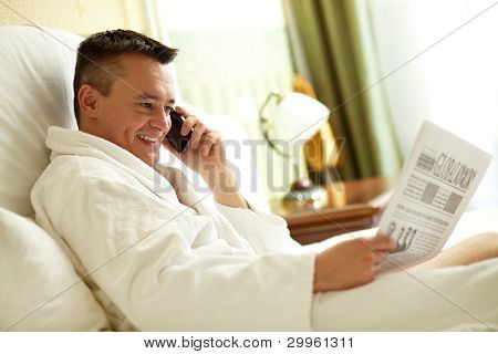 Handsome man in bathrobe talking by the phone while reading newspaper in bed