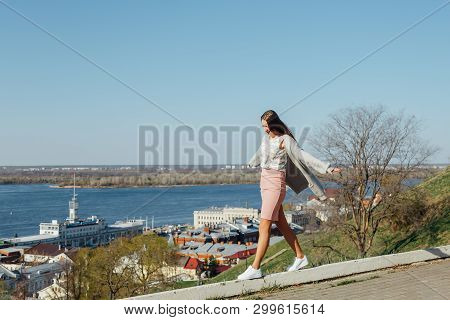 Fashionable Girl Is On The Parapet, Balancing. Fashionable Tourist Girl Walking Along The Blue Water