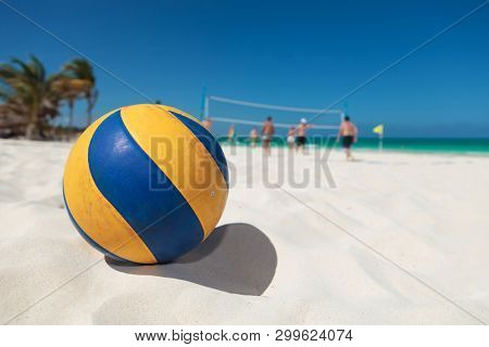 closeup of a volley ball with people in the backgrund playing on the beach, in cancun, mexico