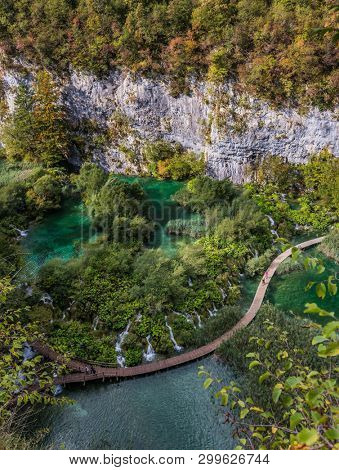 Autumn trip to Croatia. Picturesque cascading lakes with azure water among the high hills. The concept of ecological and active tourism. Wooden flooring for tourists