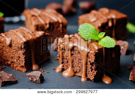 Chestnut Brownies With Chocolate Icing On A Black Background