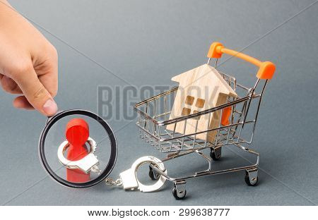 Magnifying Glass Is Looking At A Person Is Handcuffed To A House On A Supermarket Cart. Financial De