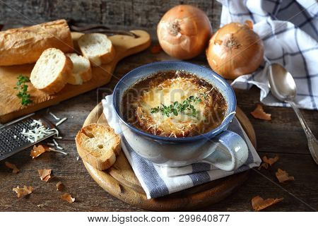French Onions Soup With Baguette, Rustic Style On Wooden Background