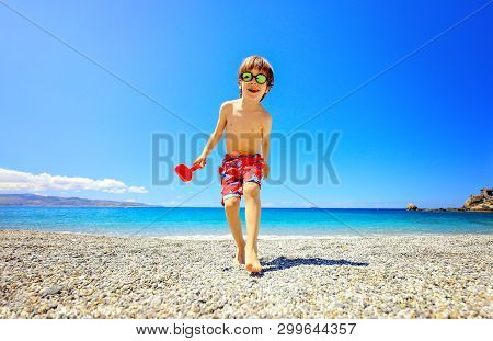 Shot Of An Adorable Little Boy Having Fun At The Beach On Vacation. Kid Wearing Sunglasses And Smili
