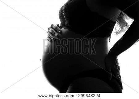 Black And White Image Of Woman Tenderly Holding Her Pregnant Belly Attentively Turning To Her Unborn
