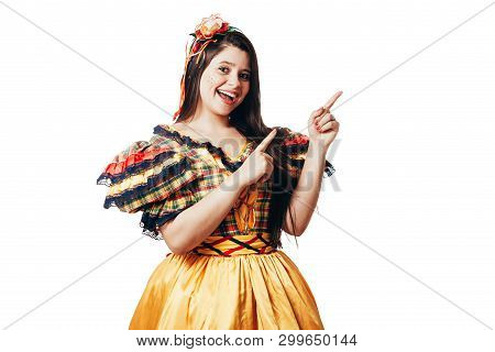 Brazilian Woman Wearing Typical Clothes For The Festa Junina Showing Something Isolated On White Bac