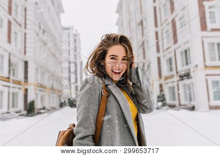 Close-up Portrait Of Ecstatic Woman In Elegant Gray Coat Standing On The Street In Snowy Day. Outdoo