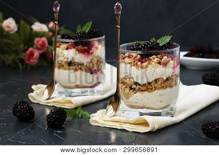 Curd Dessert With Blackberries And Cookies In Glass On A Dark Background