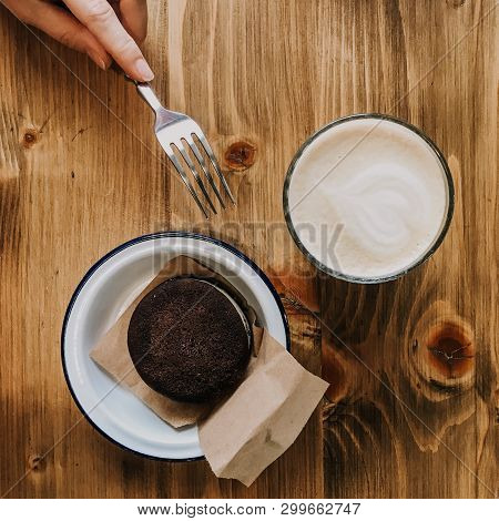 Cup Of Coffee And Chocolate Cake On Wooden Table. Hand With A Fork Touching A Cake. Squred Photo Vin