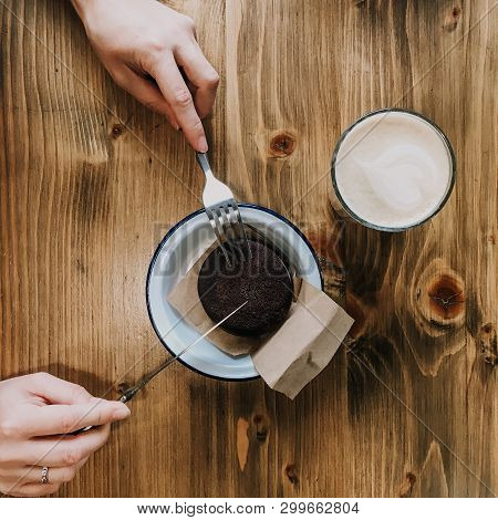 Cup Of Coffee And Chocolate Cake On Wooden Table. Hands With A Fork And A Knife Cutting A Cake. Squr