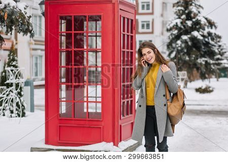 Smiling Girl In Elegant Attire Talking On Smartphone While Standing Near British Phone Booth In Wint