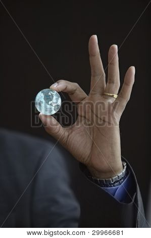 Hand holding small globe