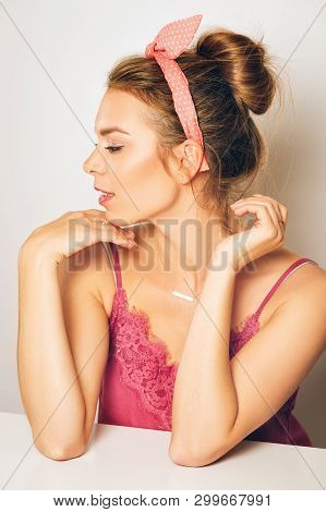 Studio Shot Of Beautiful Young Woman With Blond Hair, Chignon Bun, Wearing Pink Cami Top , Posing On