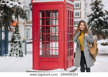 Stunning Brunette Woman In Yellow Cardigan Standing Near British Call-box In Winter Day. Outdoor Pho