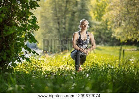 Young, Blonde Fit Woman In Black Sports Tights Doing Her Training In The Nature By The River. Fitnes