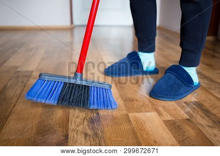 Young Woman, Wife In Blue Slippers Using Indoor Blue Broom For Hardwood Floor Cleaning. Spring Clean