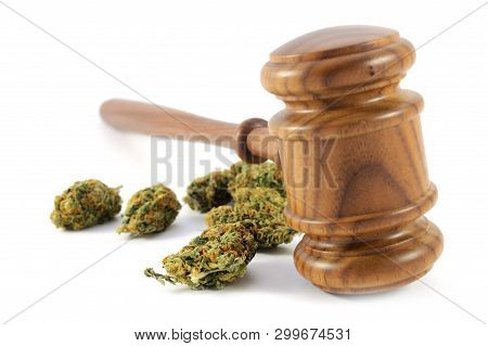 Conceptual Image Of Legalized Weed Laws Using A Wooden Gavel With Some Fresh Marijuana Isolated Over