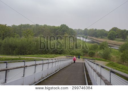 Person Traveller Wearing A Rain Coat On A Rainy Dat In A Green Park, Hiking Lifestyle