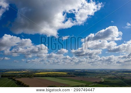 A Dreamlike Blue Sky With White Sheep Clouds Over Green And Yellow Fields