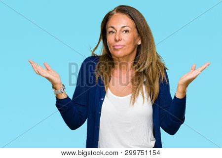 Beautiful middle age casual adult woman over isolated background clueless and confused expression with arms and hands raised. Doubt concept.