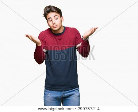 Young handsome man over isolated background clueless and confused expression with arms and hands raised. Doubt concept.