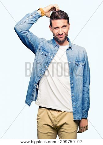 Handsome man with blue eyes and beard wearing denim jacket confuse and wonder about question. Uncertain with doubt, thinking with hand on head. Pensive concept.