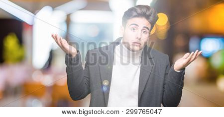 Young elegant man wearing winter coat over isolated background clueless and confused expression with arms and hands raised. Doubt concept.