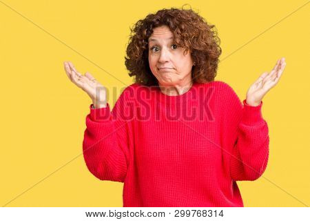 Beautiful middle ager senior woman red winter sweater over isolated background clueless and confused expression with arms and hands raised. Doubt concept.