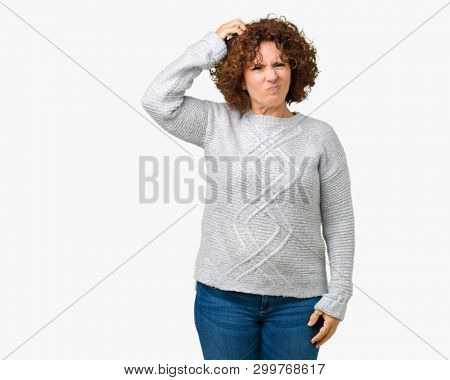 Beautiful middle ager senior woman wearing winter sweater over isolated background confuse and wonder about question. Uncertain with doubt, thinking with hand on head. Pensive concept.
