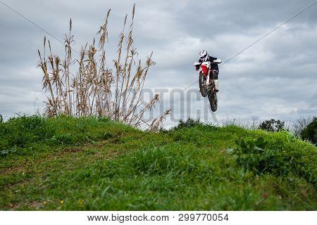 Enduro Bike Rider In Action. Jump On Mud And Grass Terrain.