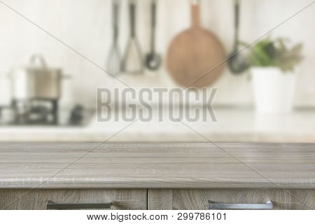poster of Blurred abstract background. Modern kitchen with wooden tabletop, space for you and display products.