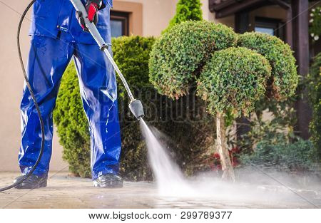 Caucasian Worker In His 30s With Pressure Washer Cleaning Residential Driveway. Garden And Home Surr