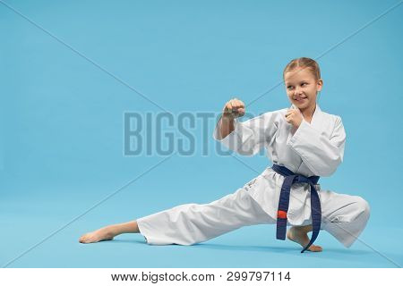 Happy Little Girl Wearing Kimono Standing In Karate Stance And Exercising In Studio. Strong Female C