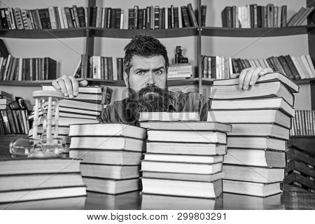 Teacher Or Student With Beard Sits At Table With Books, Defocused. Man On Serious Face Between Piles