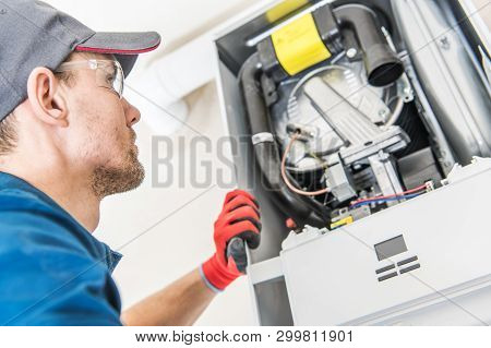 Technician And The Heater Issue. Caucasian Worker Looking Inside Central Gas Heater Trying To Fix Th