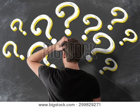 Rear View Of Puzzled Man In T-shirt Scratching His Head In Confusion Against Blackboard Filled With