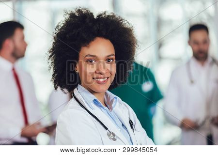 Portrait Of African American Female Doctor On Hospital Looking At Camera Smiling.