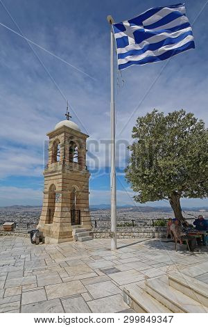 Athens, Greece - May 02, 2015: Bell Tower Greek Flagpole And Olive Tree At Top Of Mount Lycabettus I