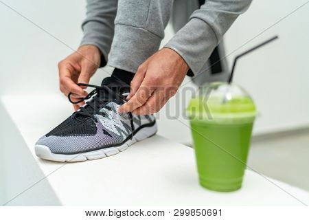Smoothie juice drink fitness man lacing running shoes, Athlete runner with green vegetable detox juice getting ready for morning run tying laces at home or gym. Fitness and healthy lifestyle concept.