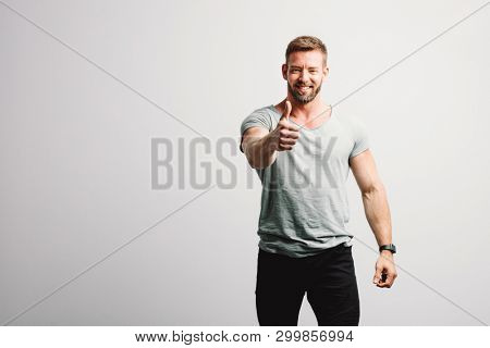 Happy man showing OK gesture and smiling. White wall background. Casual portrait.
