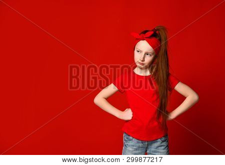 Cute Little Red-haired Girl Sulking And Frowning While Holding Hands On The Waist, Offended And Disa
