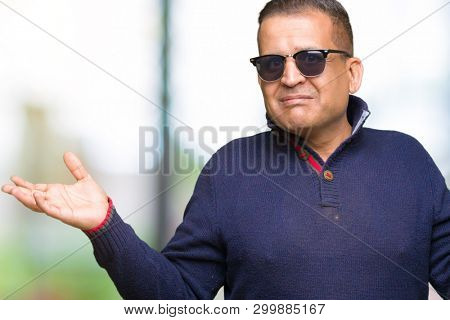 Middle age arab man wearing sunglasses over isolated background clueless and confused expression with arms and hands raised. Doubt concept.