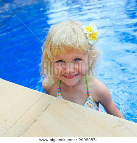 Happy little girl in a swimming pool looking at the camera smiling