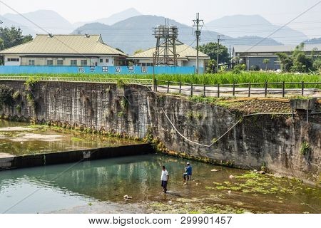 Nantou, Taiwan - April 7th, 2019:people fishing at a dirty ditch at Puli township, Nantou, Taiwan, Asia
