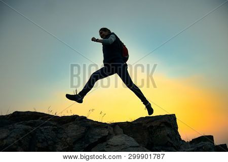 Young Woman Traveler Jumping over Rocks while Hiking with Backpack on the Beautiful Trail in the Mountains at Warm Summer Sunset. Travel and Adventure Concept.
