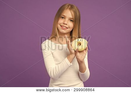 Do you want a bite Happy kid with junk food. Child smile with donut on violet background. Little girl with glazed ring doughnut on purple background. Food and dessert. Childhood and childcare. poster