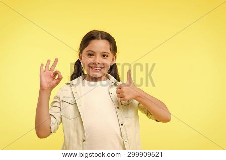 Excellent Quality. Kid Girl Shows Thumb Up And Ok Gesture Yellow Background. Child Highly Recommend