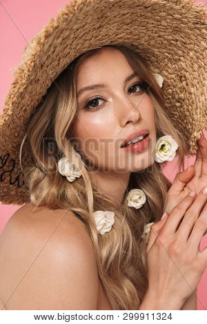 Beautiful young topless blonde woman with long hair wearing straw hat standing isolated over pink background, posing with flowers poster