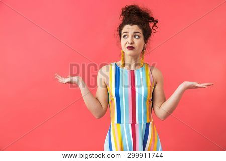 Portrait of a lovely confused woman wearing striped dress standing isolated over pink background, shrugging shoulders